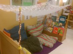 Use curtain rods taped to the book cases, a curtain, and twinkly lights to create a more cozy book area for the class library. SOOOO cozy!