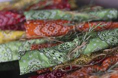 Talheres envolvidos em guardanapos de bandana da Couvert em diversas cores e fechados com alecrim e um lacinho e alecrim!