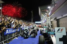 Fireworks explode as Nico Rosberg celebrates winning the Singapore Grand Prix in parc ferme by standing on his car