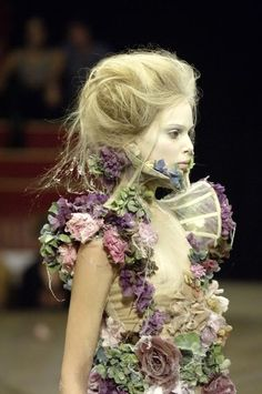 An ethereal, fairy dress by Alexander Mcqueen featuring spider webbing and clusters of purple, blue, and green flowers on shear nude fabric. Possibly chiffon.