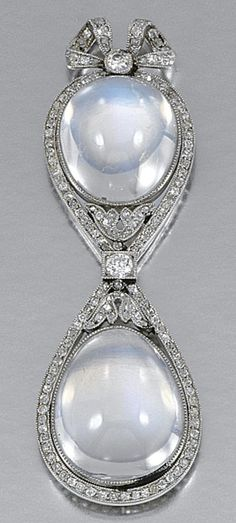 MOONSTONE AND DIAMOND PENDANT, CIRCA 1910.  Decorated to the front with two cabochon moonstones within a millegrain tied ribbon bow frame highlighted with circular- and rose-cut diamonds, to a later flattened curb link chain, length approximately 430mm.