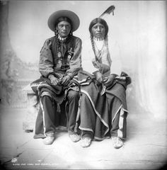 Native Americans (Ute), one identified as Pee Viggi, sit and pose for a studio portrait. They wear braids, earrings, choker necklaces, cotton shirts, leather leggings, beaded moccasins and hold woven blankets. The woman wears a bone breastplate and a feather hair ornament. Pee Viggi wears a hat and a ribbon decorated with gold pins or badges.