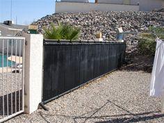 Heliocol solar pool heating panels installed on pool fence.
