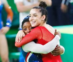 US gymnast Simone Biles and her compatiot Alexandra Raisman celebrate after the women's individual all-around final of the Artistic Gymnastics at the Olympic Arena during the Rio 2016 Olympic Games in Rio de Janeiro on August 11, 2016.