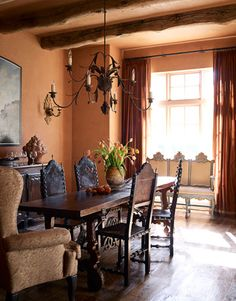 "The dining room wall color was inspired by a terra-cotta hotel room in Provence. A graceful rusted-iron chandelier is a perfect match for the very narrow 18th-century Italian table. The settee is one of the few painted-wood pieces in the house — ""and it's the prettiest painted wood you've ever seen,"" Cummings says."