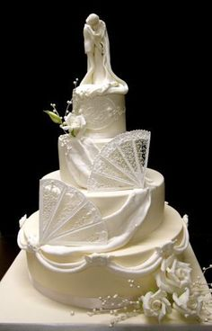 Ivory and white wedding cake with Royal Icing fans and roses Figurine is handmand (modelpasta) and edible