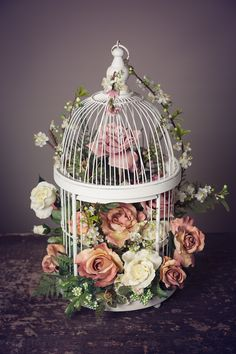 Beautiful floral wedding centerpiece for guest tables or gift and guestbook table featuring silk roses in a white bird cage