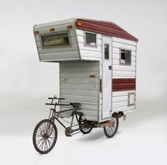 Not real, unfortunately. The Camper Bike is a sculptural piece by Brooklyn artist, Kevin Cyr.