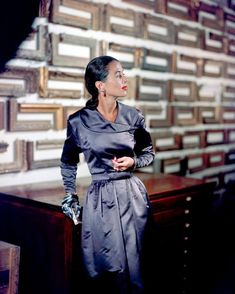 1947 --- Fashion model Sabine wears a silver evening dress by Pauline Trigere on a framing shop's stairway. --- Image by © Genevieve Naylor/Corbis