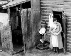 May 1936: Primitive housing conditions in Collingwood. This house had a corrugated iron makeshift bathroom, and external tap as the only water supply
