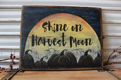 Shine on Harvest Moon sign is hand-painted on two distressed cedar pieces that have been joined in the back with wood screws. Perfect for your fall decor. Can be placed on a shelf, in a picture stand, or simply hang it on the wall. It would look cute on a table surrounded with pumpkins and fall leaves! Base-coated with black, the sky has been highlighted with blue. The full moon contains warm white, yellow, orange and a touch of red acrylic paint. The entire top has been heavily sanded to…