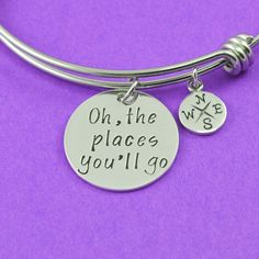 """The perfect anniversary gift! The stainless steel bangle features a 3/4"""" sterling silver charm hand stamped with the coordinates of your favorite place. Hanging from the bangle is also a sterling silv"""