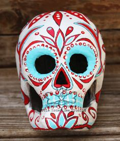 beautiful paper mache skull has been hand painted in the traditional Mexican folk art style celebrating el Dia De Los Muerto