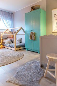 Niebieska szafa i łóżko-domek w pokoju dziecięcym