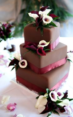wedding cake, chocolate frosting with calla lillies and red ribbon