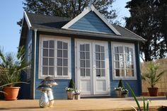 Blau lasiertes Clockhouse Gartenhaus mit liebevoll dekorierter Holzterrasse. http://www.gartenhaus-gmbh.de/
