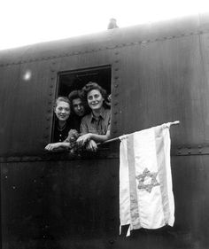 These Jewish youngsters are on their way to the British Mandate after being released from Buchenwald concentration camp, June 5, 1945, near Weimar, Germany. The girl on the left is from Poland, the boy in the center is from Latvia, and the girl holding the Zionist flag is from Hungary. (AP Photo and original caption)