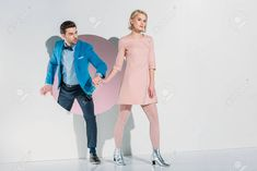 fashionable young couple holding hands and walking through hole on grey , Couple Holding Hands, Young Couples, Cuddling, Walking, Grey, Coat, Jackets, Fashion, Couple Hands