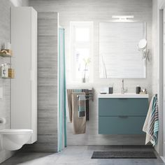 A light grey small bathroom with a white high cabinet, a mirror and a grey wash-stand with two drawers.