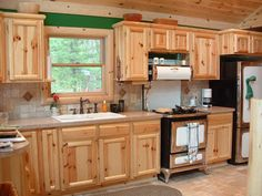 Love this kitchen! The oven and refrigerator add to its uniqueness. Would love to have a cabin with this in it. Their wood work is beautiful!