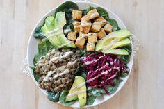 Lentil ,Tempeh & Spinach Salad Bowl, Vegan + Gluten-Free. Macro bowl with avocado, sauerkraut, tempeh, lentils, spinach. Tahini dressing, lemon, maple syrup.