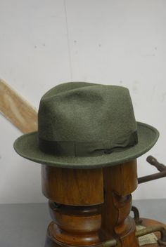This is a beautiful fedora.  We date it to around the early 1960s  Made in Italy by Barbisio  Made of a multi shade green fur felt  A grosgrain ribbon with bow detail wraps around the bottom of the crown. Green in colour and 1 1/16 in height.  The brim is a snap down brim and the edges are overwelt in style.  The hat has a satin style liner and a leather sweatband.  Condition overall is good, some light wear on the liner and the shape might want a bit of working just to get a perfect…