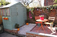 Garden patio with pale blue shed and bright colours