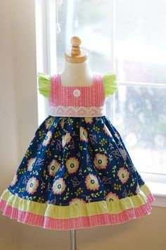 The Danielle Dress was specifically designed as a girls BACK-to-SCHOOL dress. The dress is full of color with a dark blue background. We just love how it is paired up with a bright pink and citrus gre Frilly Dresses, Pretty Dresses, Girls Dresses, Toddler Dress, Baby Dress, Little Girl Outfits, Kids Outfits, Frock Models, Easter Dresses For Toddlers