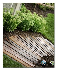 Pallet Pathway: Remove the boards from an old pallet & use a circular saw to taper one end of the plank thinner than the other- approximately 1-2 inches according to the degree of turn needed.   Stain with any wood stain (or several, to create the different wood tones). Finish with a coat of polyurethane.