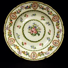 An 18th Century Sevres Porcelain Dish Decorated in the Neo-Classical Style. The Border with Pink Oval Panels with Pearls and a Roses to the Center, the Panels are Linked by Loose Swags of Roses Tied with Pink Bows. The Rest of the Decoration Consists of More Roses and Corn Flower within Laurel Wreath Borders. The Base with the Royal French Cypher, Interlaced LLs with 'ee' for 1782 and the Painter's Mark 'nq' for Niquet as well as the Mark of the Gilder Vincent '2000'.