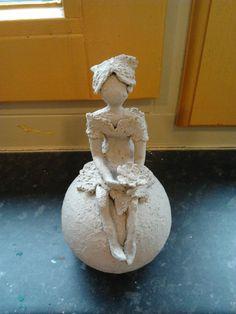 Meisje op bol uit eerste oven-bak, ongeglazuurd. (aardewerk)