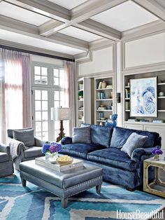 All the blues in the house started with the vivid fabric on the family room sofa, Kravet's Venetian. A bookshelf conceals a door to the back stairs. Walls are painted in Kestrel White to contrast with the Mega Greige trim, both by Sherwin-Williams. Reagan chairs in Kravet's Marcellus and Rancho ottoman, Bernhardt.    - HouseBeautiful.com