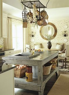 Warm kitchen with giant french blue worktable - love the wallpapered seating area