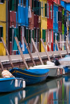 The brilliant colours of the houses are reflected in the waters of the canals in Burano, Italy.