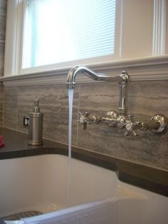 a wall mount traditional style faucet looks great with a white fire clay farmhouse sink in the kitchen