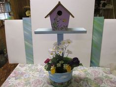 This flower pot mini plant stand also with a decorative bird house ( if you like ) uses a plastic ice cream tub that nicely fills the roll of a plant pot.…