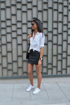 9 maneiras de usar saia de couro. Camisa branca com nozinho na cintura, minissaia, tênis branco
