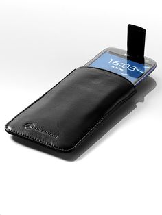 The stylish sleeve for your Samsung Galaxy: the elegant black sleeve is made of grained cowhide.  A particular feature of this sleeve is a magnetic tab that makes it easier to remove the device while also serving to fasten the sleeve  . An ultra-soft lining protects your smartphone against scratches. The front is decorated with a discreet embossed logo. Embossed Logo, Mercedes Benz, Zip Around Wallet, Smartphone, Samsung Galaxy, Laptop, Elegant, Stylish, Sleeve