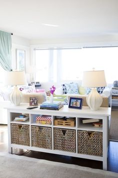 white sofa table with storage space storage baskets family games photos lamps against the back of the sofa