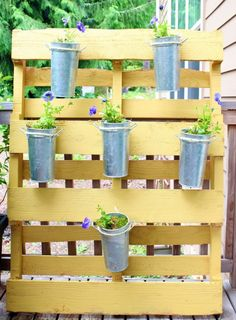 Using a shipping palette is an easy way to store planters vertically.  Staining, painting and faux finishing can add class to this eco-friendly look.