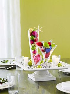 Cake Plate Centerpiece.        For this simple centerpiece, fill a few glasses with colorful ornaments and arrange on a footed cake plate. Cover the base of the cake plate with extra ornaments, jingle bells, and a few candles for ambiance.