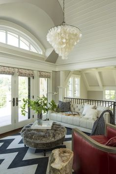 Gorgeous living area with barrel vaulted ceilings and arched window. The glass patio doors are dressed with patterned roman shades. The walls are painted Revere Pewter by Benjamin Moore. A tufted ivory colored sofa stands against the iron stair railings topped with a gray pillow, white pillows and a Mongolian wool pillow.