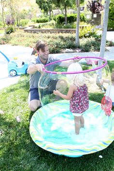 Giant bubbles with bubble solution in a baby pool and a hula hoop