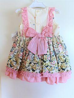 Kaunis kukkakuvioinen valkoinen mekko, jonka helma on vaaleanpunainen ja jonka yläosassa on vaaleanpunainen röyhelö sekä rusetti.