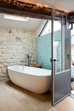 Un mélange original  :  mur de pierres, zeliges turquoise, porte atelier, baignoire ovale | original bathroom