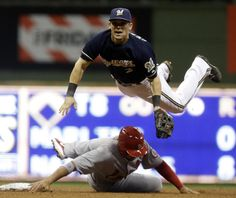 Milwaukee Brewers second baseman Scooter Gennett leaps over St. Louis Cardinals' Jon Jay after throwing to first to complete the double play on a ball hit by David Freese during the fourth inning of a baseball game Friday, Sept. 20, 2013, in Milwaukee. (AP Photo/Morry Gash)