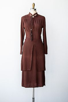 1930s chocolate brown dress with a double layer skirt and tassel neckline. Buttons down the center of the bodice and darting at the bust add detail. Via Adored Vintage.