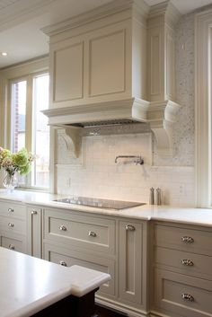 light gray kitchen cabinets paired with honed marble countertops and two types of kitchen backsplash: White glass mosaic tiles and white subway tile backsplash. Light gray wood kitchen hood with swing-arm pot filler and modern gas cooktop.