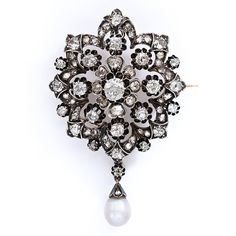 A regal treasure dating back to the mid-19th century. A sparkling diamond snowflake crafted in dark oxidized silver over rose gold with a dangling, soft white oriental (natural) pearl looks splendid either as a brooch or necklace pendant. A superb and stunning antique adornment. Over 3.50 carats total diamond weight. 1 1/2 inches high (without pearl drop) by 1 3/8 inches wide.