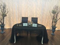 Love this wooden sweetheart table draped with black lace and gold accent pieces. Mr and Mrs sign. Manzanita with champagne paper flowers